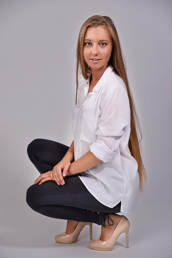 Jong blond meisje met lang haar in een wit overhemd royalty-vrije stock foto's