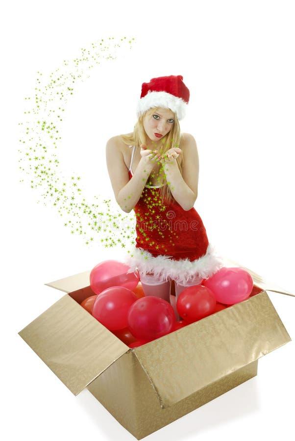 Jong blond santameisje in een doos blazende kussen stock afbeeldingen
