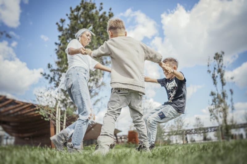 Jong blonde die mum, met haar zonen bij park wervelen zich omdraaien die royalty-vrije stock foto