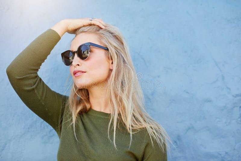Jong blonde die in zonnebril weg kijken stock afbeeldingen