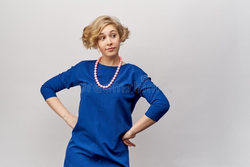 Jong blonde met korte haar en krullen, die voor Studio het schieten stellen Zij ` s die een blauwe kleding en uitstekende parels  stock fotografie