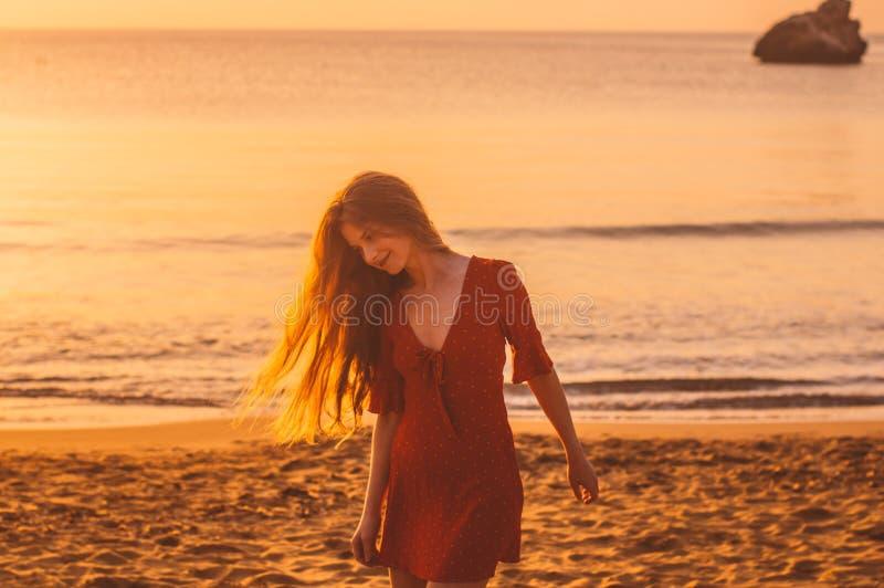 Jong blondemeisje dat in rode kleding in de avond op het strand loopt royalty-vrije stock afbeelding