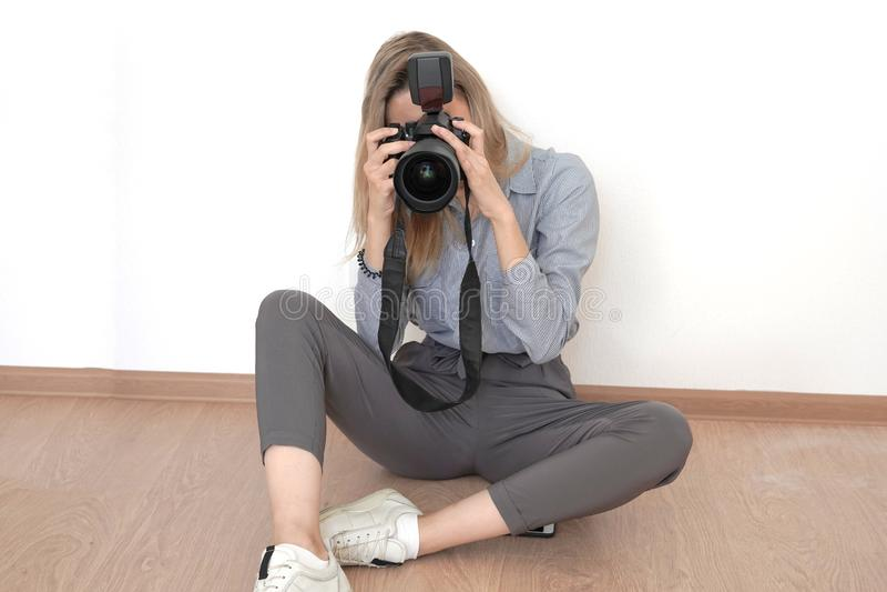Jong blondemeisje die beelden nemen die op de vloer in de studio zitten royalty-vrije stock foto