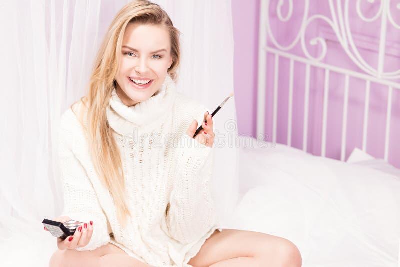 Jong blondemeisje die make-up doen royalty-vrije stock afbeelding