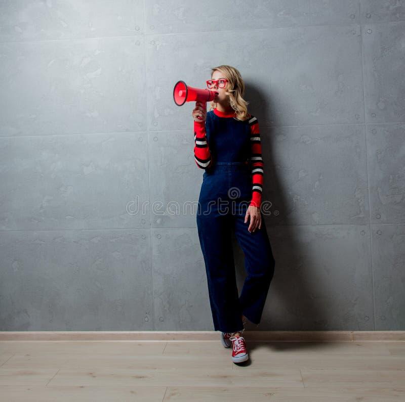 Jong blondemeisje in jeans die zich met megaphoone kleden royalty-vrije stock foto's