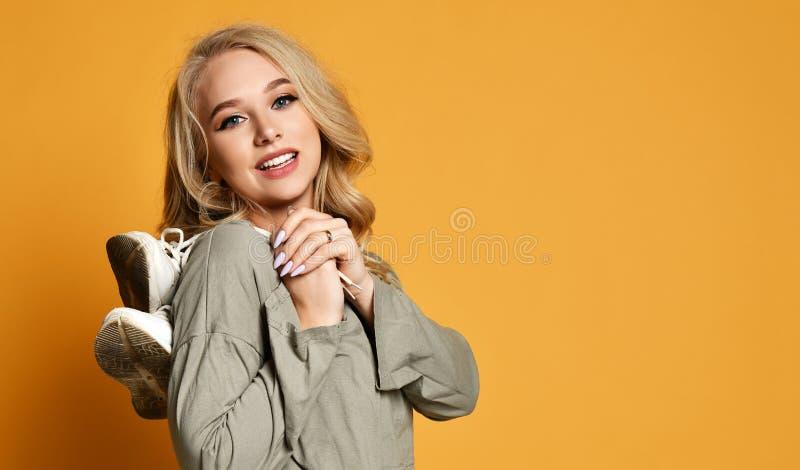 Jong blondemeisje in korte blousegang ergens met oud paar vuile schoenen op haar schouder royalty-vrije stock fotografie