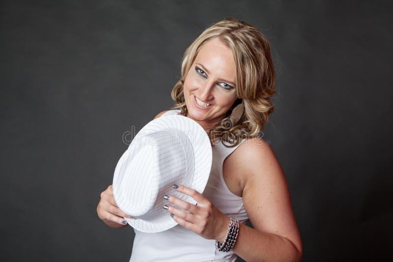 Jong blondemeisje met de donkere hoed van de samenstellingsholding royalty-vrije stock foto's
