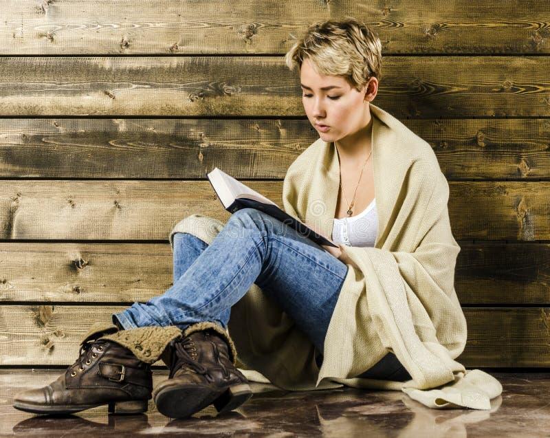 Jong blondemeisje met kort haar die met een algemene lezing een boek hebben behandeld royalty-vrije stock foto