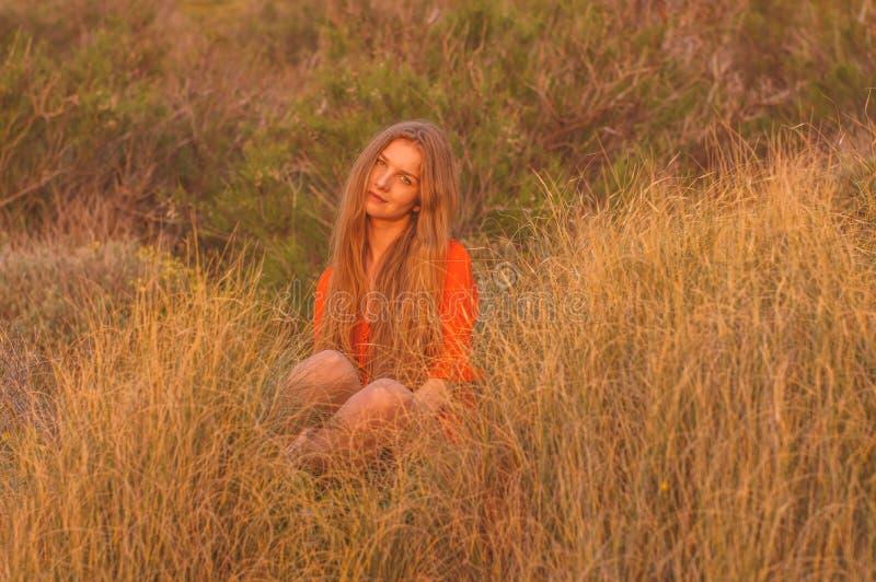 Jong blondemeisje in rode kledingszitting op gras royalty-vrije stock afbeeldingen
