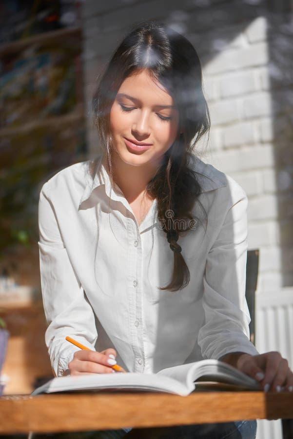 Jong brunette bij de koffie stock afbeelding
