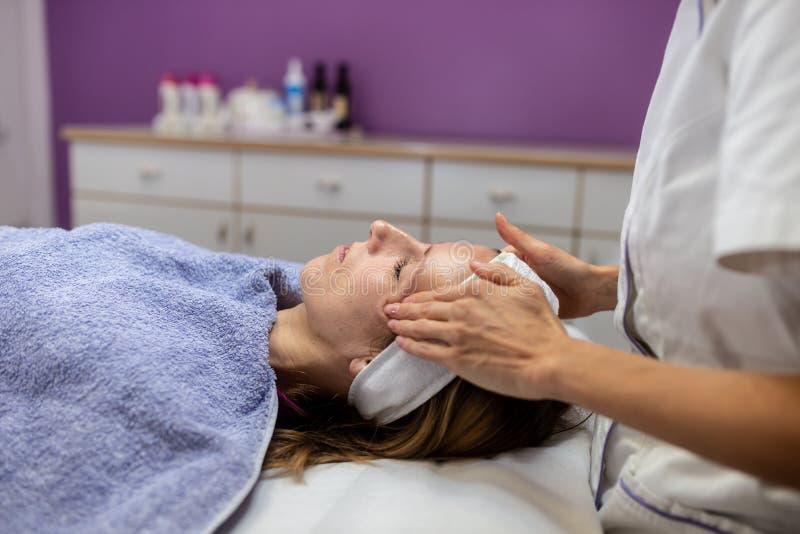 Jong brunette die op massagelijst liggen die een gezichtsmassage krijgen royalty-vrije stock foto's