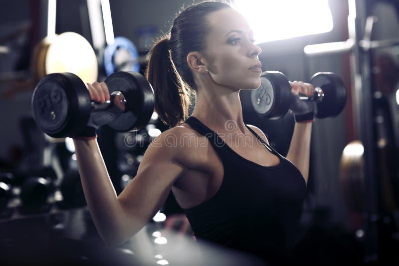 Jong brunette die sommige gewichten opheffen en aan haar bicepsen binnen werken royalty-vrije stock foto