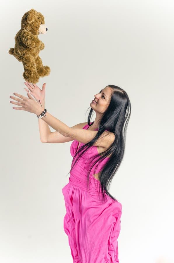 Jong brunette in een lange roze kleding royalty-vrije stock foto's