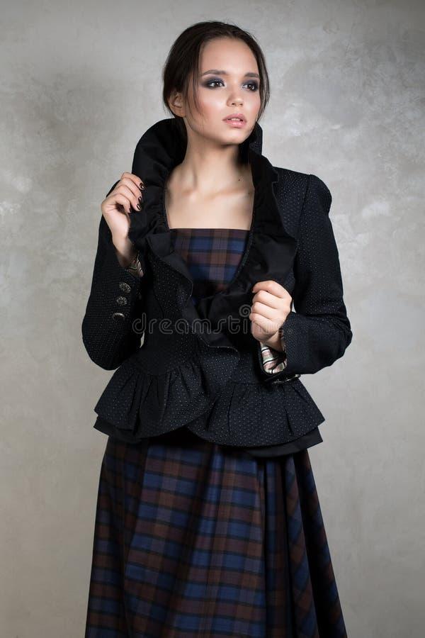 Jong brunette met verzameld haar in een donkere plaidkleding en jasje met hoge kraag die zich op grijze achtergrond bevinden stock foto's