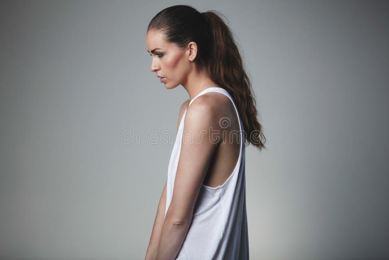 Jong brunette in mouwloos onderhemd stock foto