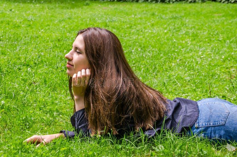 Jong charmant meisje de tiener met lang haar die en op het groene gras liggen rusten terwijl het lopen in het park in Lviv Striys stock fotografie