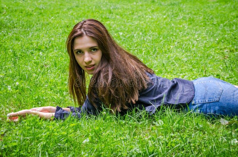 Jong charmant meisje de tiener met lang haar die en op het groene gras liggen rusten terwijl het lopen in het park in Lviv Striys stock foto