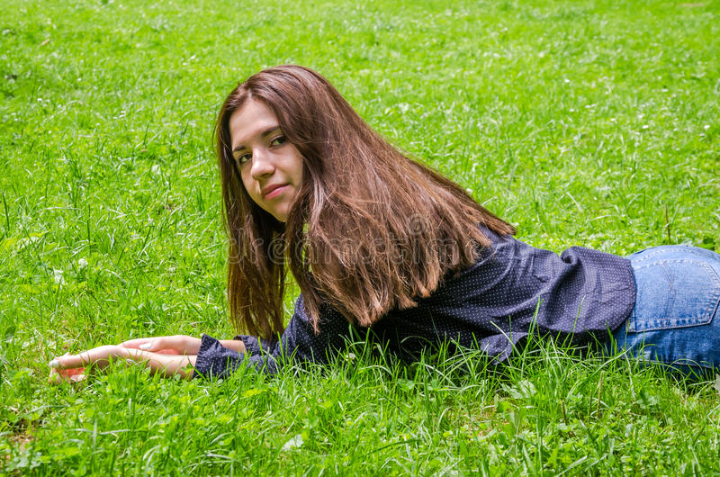 Jong charmant meisje de tiener met lang haar die en op het groene gras liggen rusten terwijl het lopen in het park in Lviv Striys royalty-vrije stock foto's