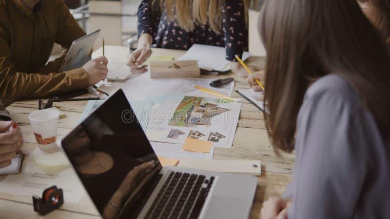 Jong creatief commercieel team in modern bureau Multi-etnische groep die mensen aan architectuurontwerp samenwerken royalty-vrije stock afbeelding
