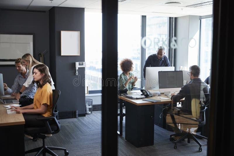 Jong creatief team die bij computers in een toevallig bureau samenwerken, dat door glasmuur wordt gezien royalty-vrije stock afbeelding