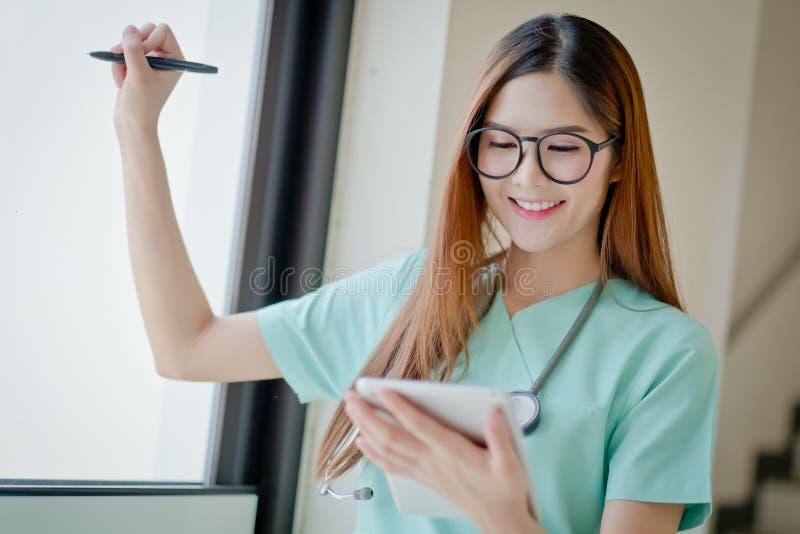 Jong de glimlachgezicht van de artsenvrouw met stethoscoop die mede tablet kijken royalty-vrije stock afbeelding