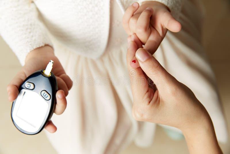 Jong de suikerniveau van het meisjes testend bloed stock foto