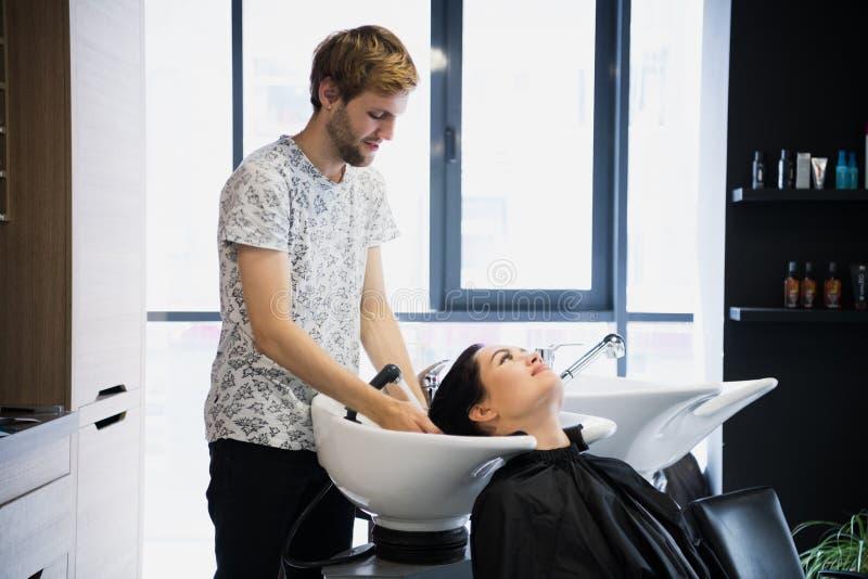Jong de washaar van de hipster mannelijk kapper van een mooie donkerbruine vrouwelijke vrouwencliënt in een zaal stock fotografie