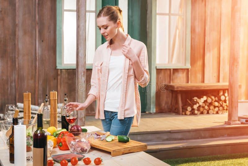 Jong de wijnglas van de vrouwenholding bij lijst met vlees en groenten in openlucht stock afbeelding