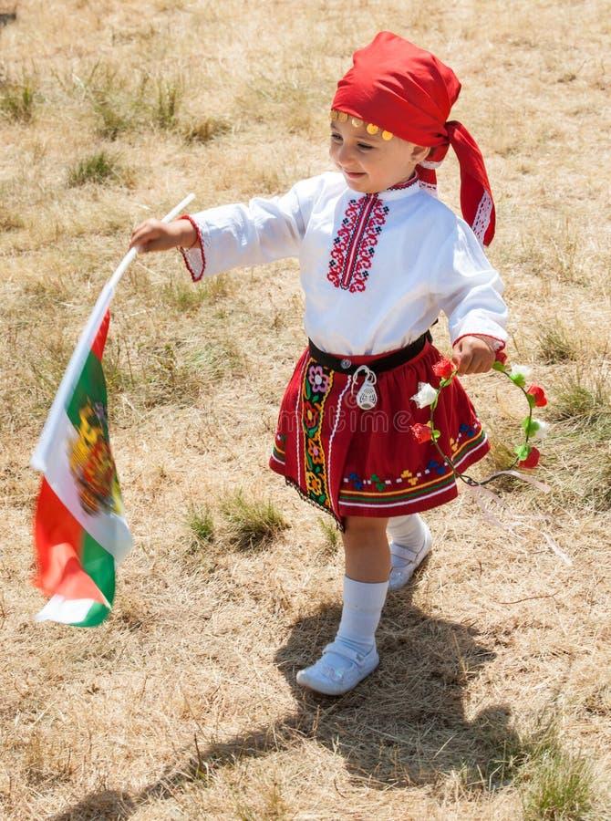 Jong deelnemersfestival Rozhen in nationaal kostuum en de Bulgaarse vlag stock afbeeldingen