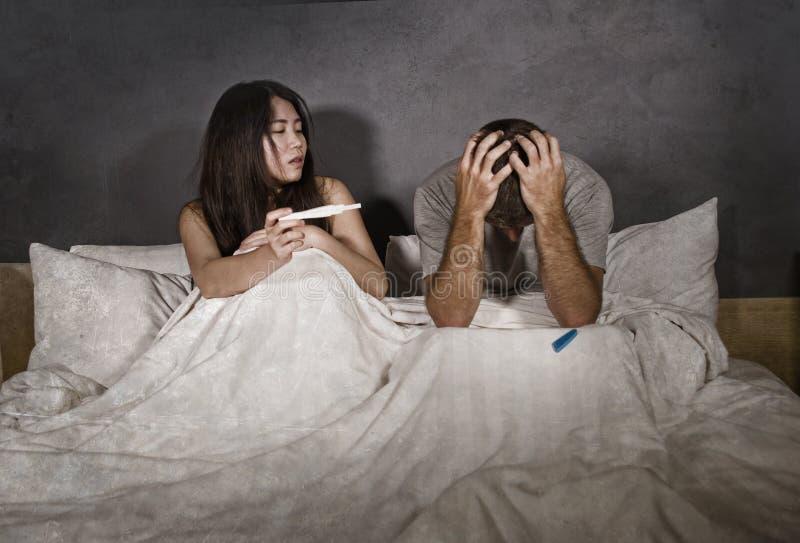 Jong die paar in bed na positief resultaat op zwangerschapstest wordt doen schrikken en wordt beklemtoond met zwangere vrouw die  stock foto