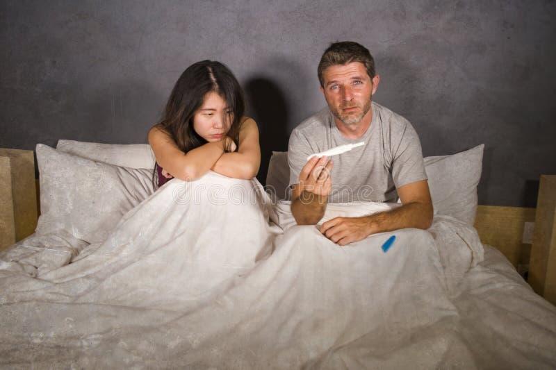 Jong die paar in bed na positief resultaat op zwangerschapstest wordt doen schrikken en wordt beklemtoond met zwangere vrouw die  royalty-vrije stock fotografie