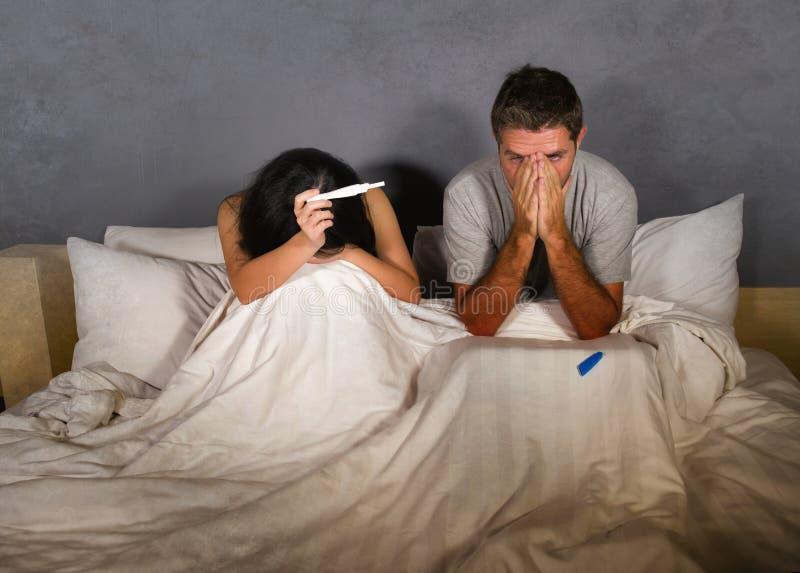 Jong die paar in bed na positief resultaat op zwangerschapstest wordt doen schrikken en wordt beklemtoond met zwangere vrouw die  royalty-vrije stock foto
