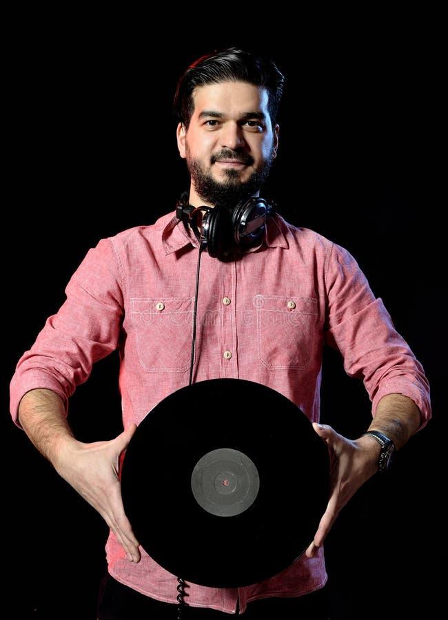 Jong DJ die in wit kostuum vinylverslag binnen houden royalty-vrije stock afbeelding