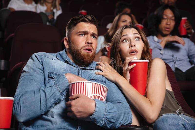 Jong doen schrikken paar die op een verschrikkingsfilm letten stock afbeelding