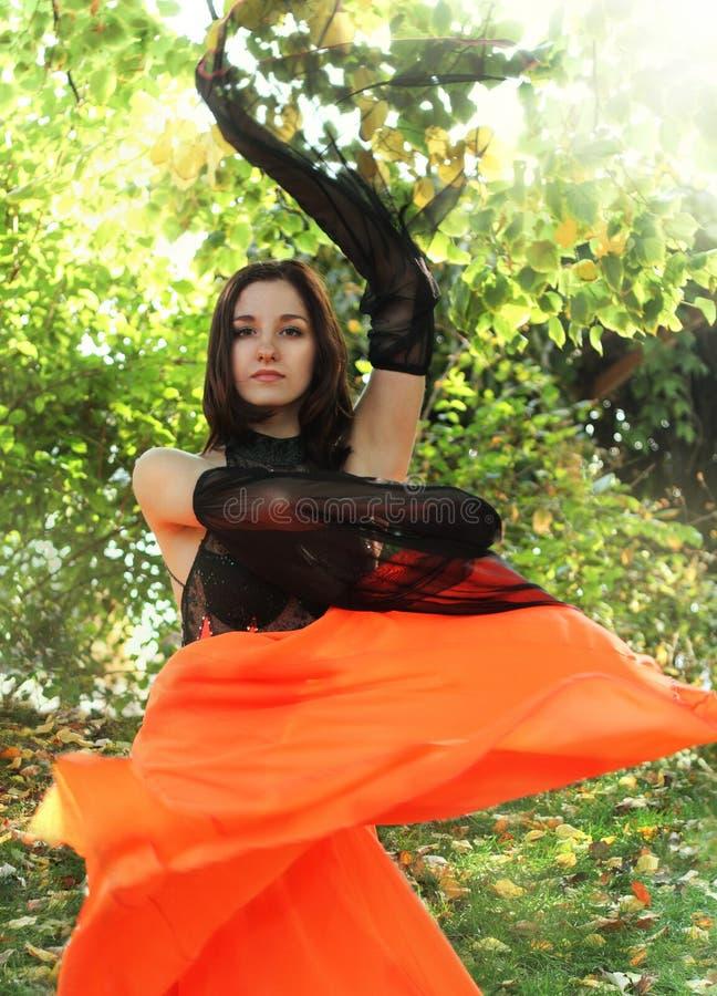 Jong donkerbruin meisje dat in de tuin danst stock afbeeldingen