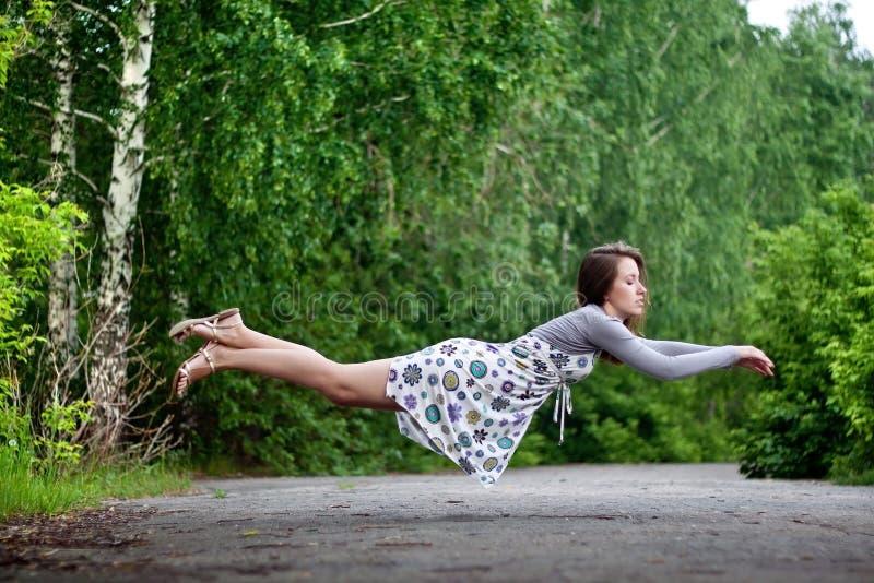 Jong donkerbruin meisje in kleurrijke kleding die in het park levitatie ondergaan royalty-vrije stock fotografie
