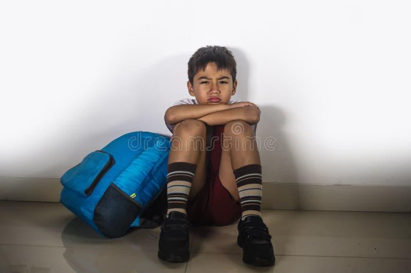 Jong droevig doen schrikken jong geitje 8 jaar oud in eenvormige school en rugzak die alleen gedeprimeerd en bang gemaakt schreeu stock fotografie