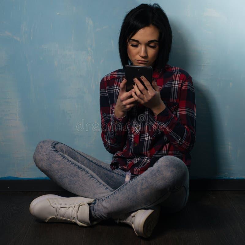 Jong droevig meisje die aan afhankelijkheid van sociale netwerken lijden die op de vloer met een smartphone zitten royalty-vrije stock fotografie