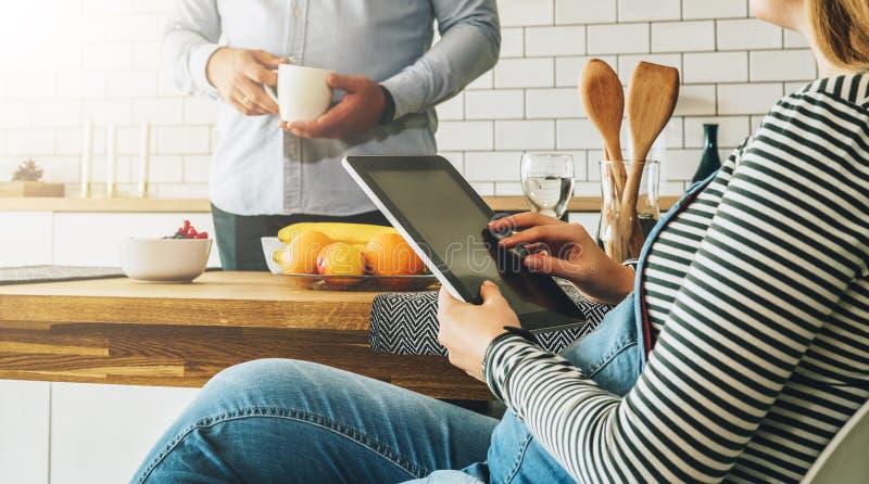 Jong echtpaar in de keuken Een zwangere vrouw zit bij een lijst en gebruikt een tabletcomputer Een mens status royalty-vrije stock foto