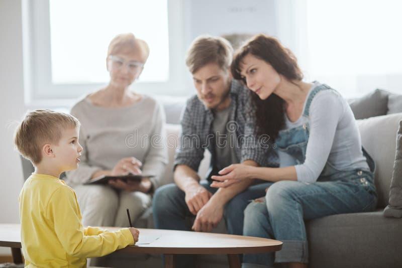 Jong echtpaar met zoon tijdens familietherapie met adviseur royalty-vrije stock afbeeldingen