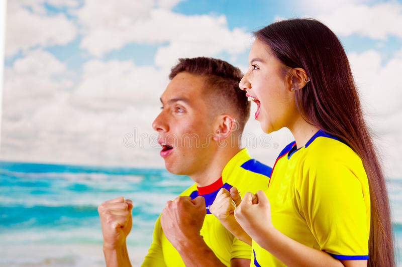 Jong Ecuatoriaans paar die het officiële overhemd die van de Marathonvoetbal onder ogen ziend camera, zeer bezet kinetisch gedrag royalty-vrije stock foto
