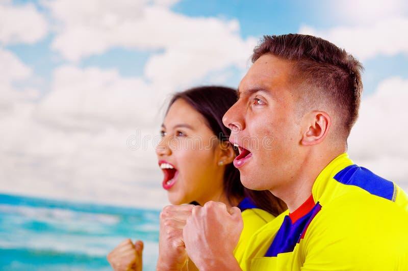 Jong Ecuatoriaans paar die het officiële overhemd die van de Marathonvoetbal onder ogen ziend camera, zeer bezet kinetisch gedrag royalty-vrije stock afbeelding
