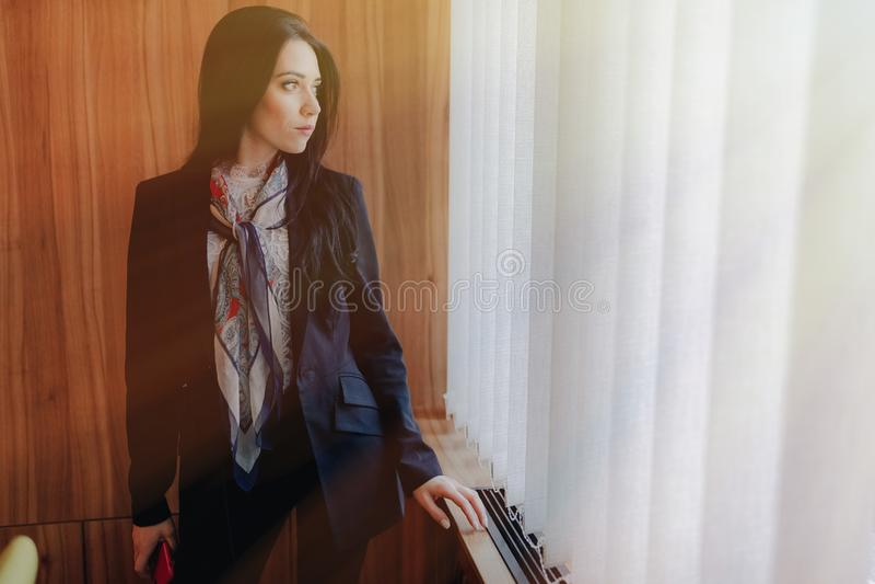 Jong emotioneel aantrekkelijk meisje in zaken-stijl kleren bij een venster met een telefoon in een modern bureau of een auditoriu royalty-vrije stock afbeelding