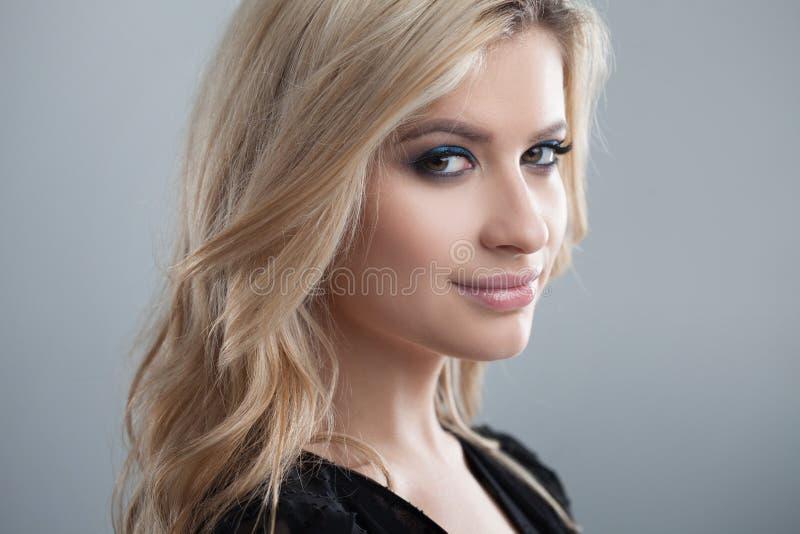 Jong en aantrekkelijk blondemeisje met glanzend golvend haar Mooi model, krullend kapsel stock foto