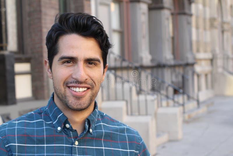 Jong en aantrekkelijk latino mannetje die in de stad glimlachen stock afbeeldingen