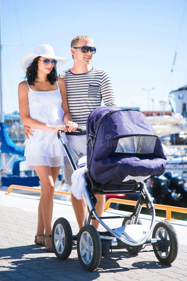 Jong en aantrekkelijk paar die met een babykinderwagen lopen royalty-vrije stock fotografie