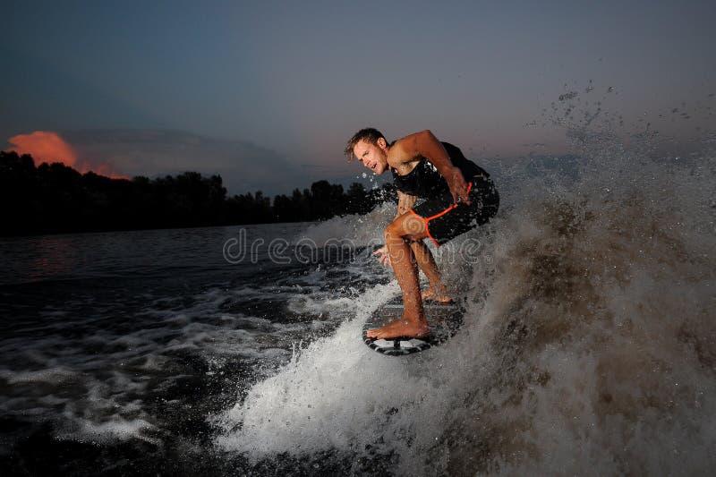 Jong en actief personenvervoer op wakesurf onderaan de rivier tijdens su stock afbeelding