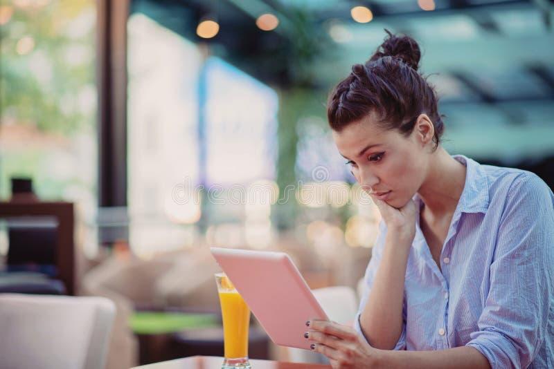 Jong en mooi meisje met notitieboekje en laptop zitting in een koffie stock foto