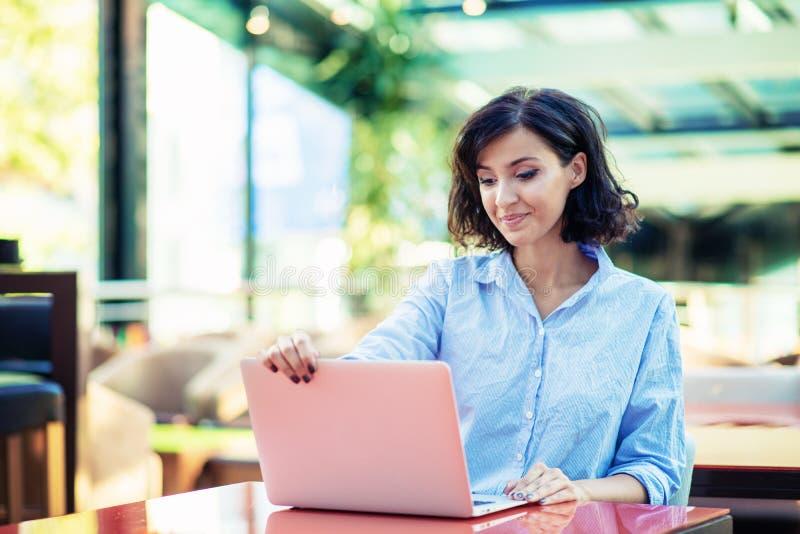 Jong en mooi meisje met notitieboekje en laptop zitting in een koffie royalty-vrije stock fotografie