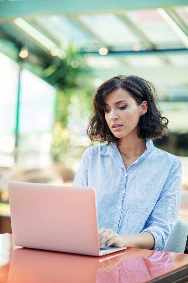 Jong en mooi meisje met notitieboekje en laptop zitting in een koffie stock afbeeldingen